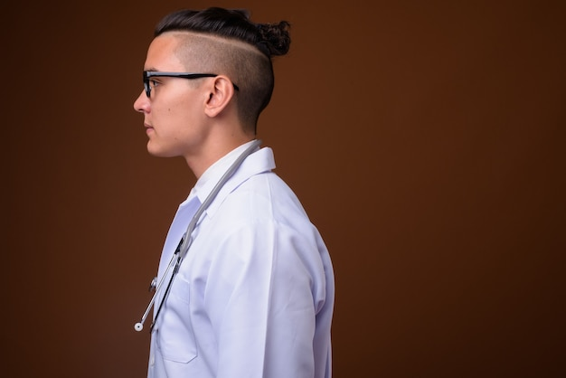 Young handsome multi-ethnic man doctor on brown