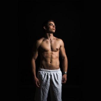 Молодой красивый мускулистый мужчина в студии на черном фоне, глядя в сторону