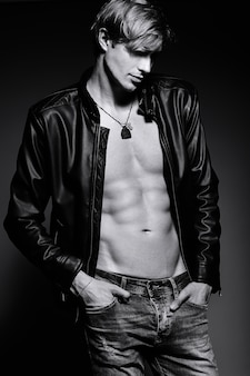 彼の腹部の筋肉を示すスタジオでポーズをとって革のジャケットで筋肉の若いハンサムなフィット男性モデル男