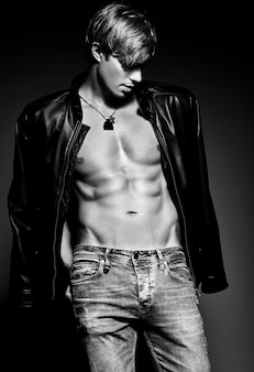 Young handsome muscled fit male model man posing in studio showing his abdominal muscles in  leather jacket