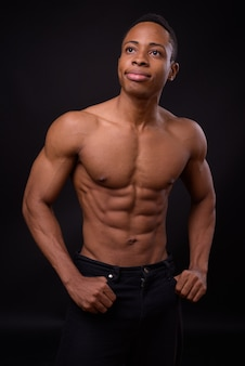 Young handsome muscular african man shirtless against black space