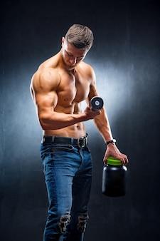 手にスポーツ栄養とダンベルを持つ若いハンサムな筋肉の男。濃い青の背景。