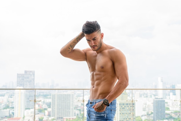 Молодой красивый мускулистый персидский мужчина без рубашки и смотрит на город
