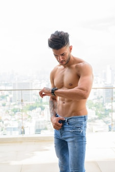 Young handsome muscular persian man shirtless checking the time against view the city