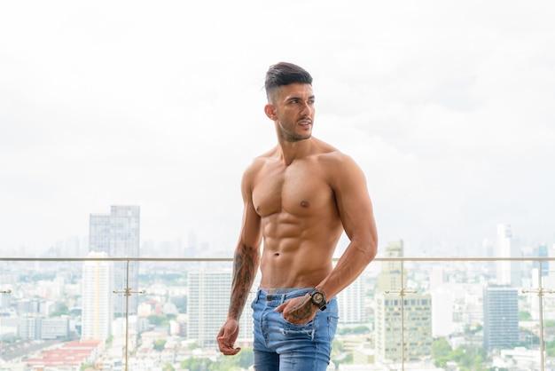Молодой красивый мускулистый персидский мужчина без рубашки думает против вида на город