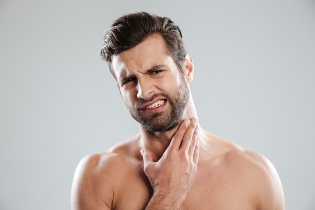 Молодой голый красавец экспериментирует с лицом перед бритьем