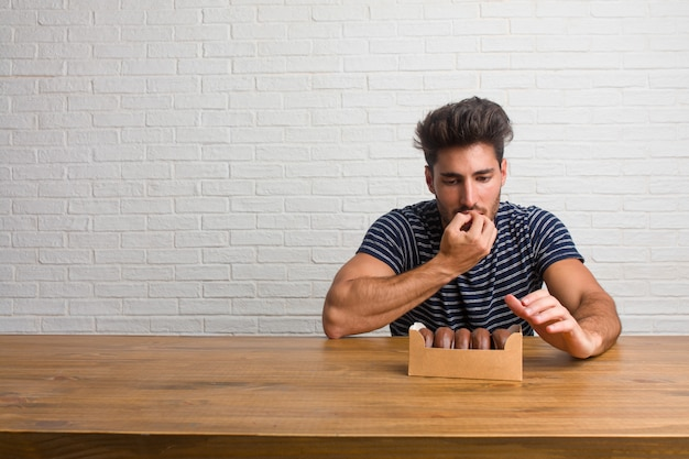 Young handsome and natural man sitting on a table biting nails, nervous and very anxious and scared