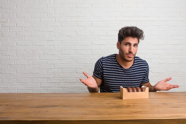 Young handsome and natural man sitting on a table doubting and shrugging shoulders