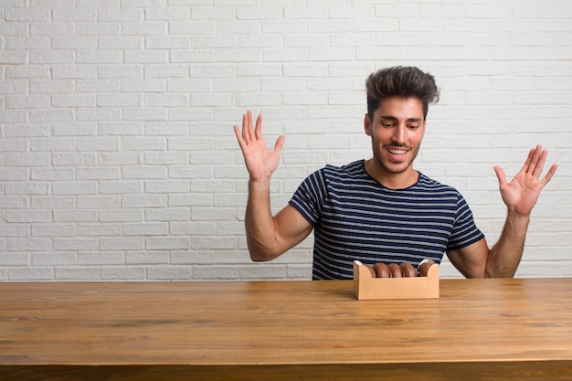 Young handsome and natural man sitting on a table screaming happy, surprised by an offer or a promotion