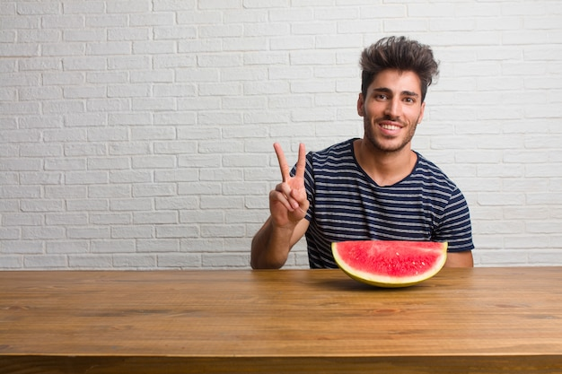 Young handsome and natural man sitting on a table showing number two, symbol of counting, concept of mathematics, confident and cheerful. eating a watermelon.