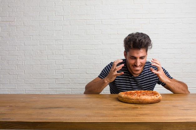 Young handsome and natural man sitting on a table very angry and upset, very tense, screaming furious, negative and crazy. eating a delicious pizza.