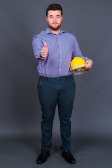 Young handsome overweight bearded businessman as engineer with hardhat on gray