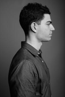 Молодой красивый персидский бизнесмен против серой стены в черно-белом