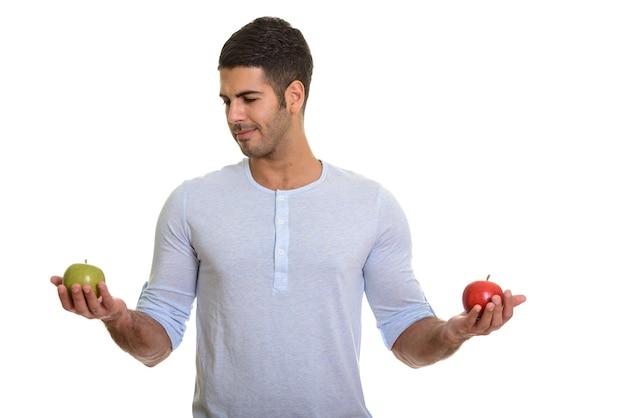 Молодой красивый персидский мужчина выбирает между красным и зеленым яблоком
