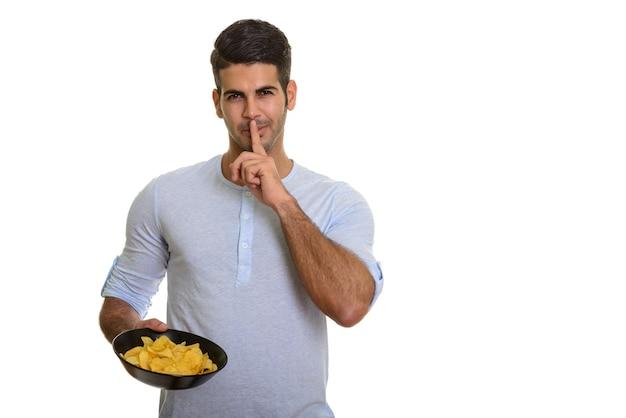 Молодой красивый персидский мужчина держит миску картофельных чипсов с пальцем на губе
