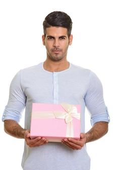 Молодой красивый персидский мужчина держит подарочную коробку