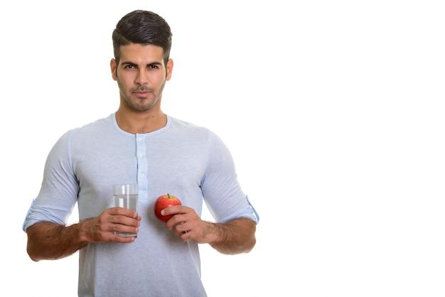 Молодой красивый персидский мужчина держит стакан воды и красное яблоко