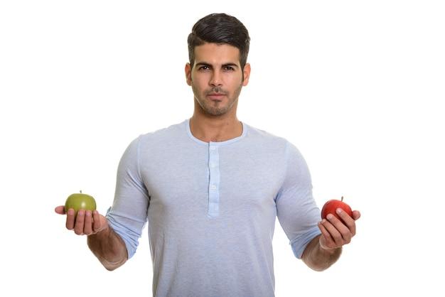 Молодой красивый персидский мужчина держит красное и зеленое яблоко