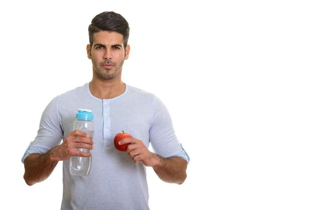 Молодой красивый персидский мужчина держит бутылку с водой и красное яблоко