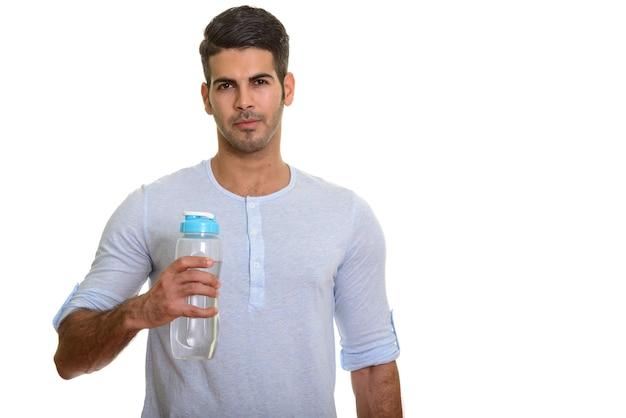 Молодой красивый персидский мужчина держит бутылку с водой