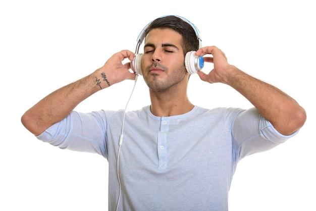 Молодой красивый персидский мужчина слушает музыку с закрытыми глазами