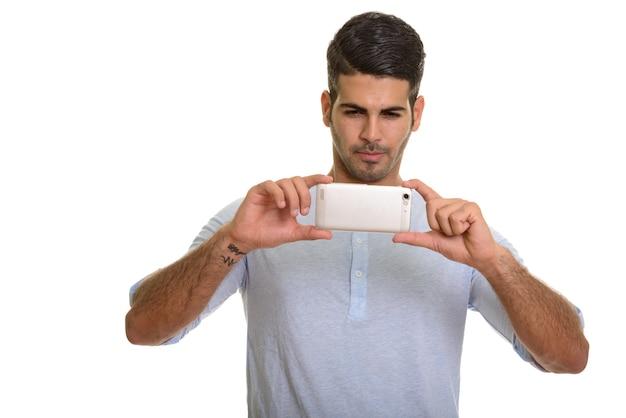 Молодой красивый персидский мужчина фотографирует с мобильным телефоном