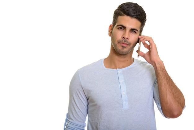 Молодой красивый персидский мужчина разговаривает по мобильному телефону