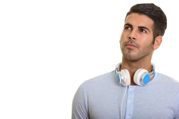 Молодой красивый персидский мужчина думает в наушниках на шее