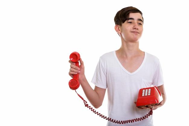 Молодой красивый персидский мальчик-подросток держит старый телефон