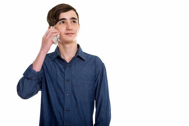 Молодой красивый персидский подросток разговаривает по мобильному телефону