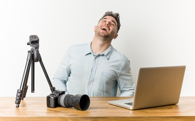 Young handsome photography laughing, neck stretched showing teeth.