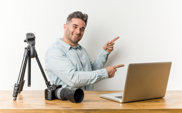 Young handsome photography teacher excited pointing with forefingers away.