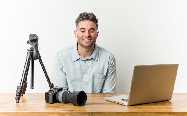 Young handsome photography teacher laughs and closes eyes, feels relaxed and happy.