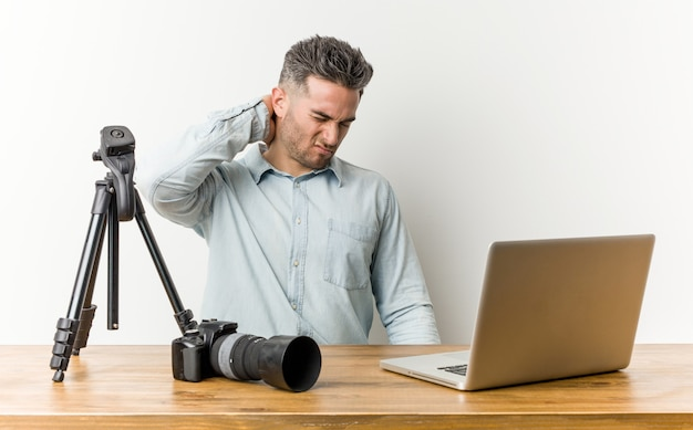 Young handsome photography teacher suffering neck pain