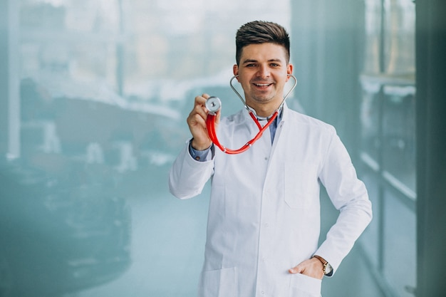 Young handsome physician in a medical robe with stethoscope