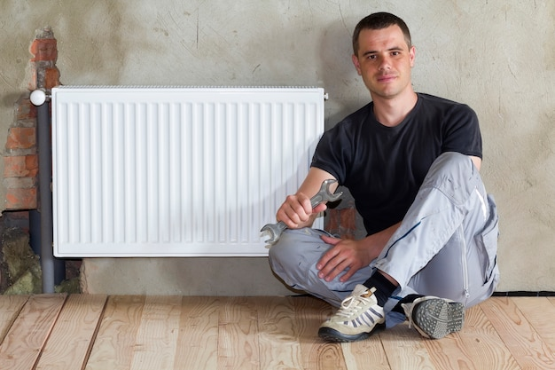 Young handsome plumber sitting on floor with wrench in hand near successfully installed heating radiator in empty room of a newly built apartment or house.