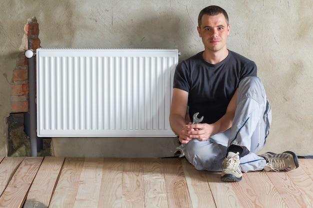 新しく建てられたアパートまたは家の空の部屋に正常にインストールされた暖房ラジエーターの近くにレンチを手にして床に座っている若いハンサムな配管工。建設、メンテナンス、修理のコンセプト