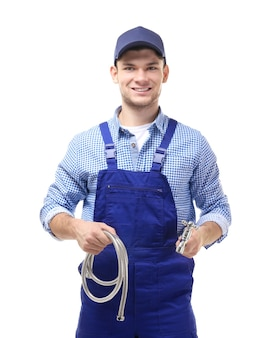 Young handsome plumber with flexible hose and tap on white background