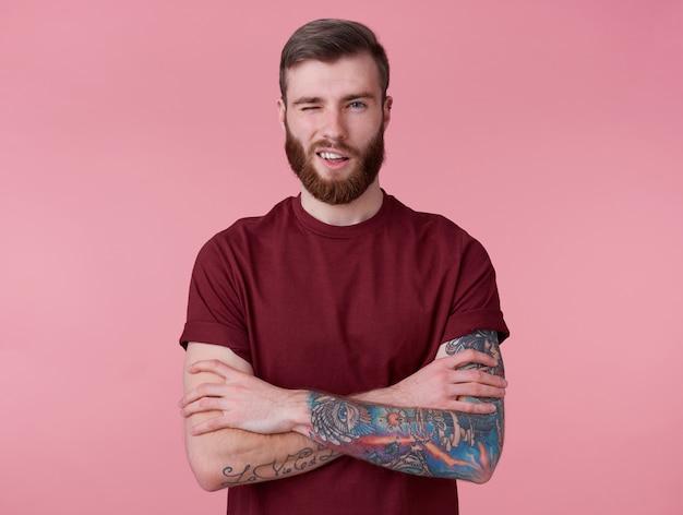 Giovane bel ragazzo barbuto rosso positivo in maglietta vuota, guarda la telecamera, ammiccante e sorride in generale, si erge su sfondo rosa e strizza l'occhio.