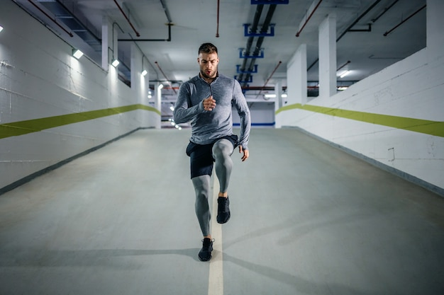 Young handsome powerful muscular caucasian sportsman in active wear running in underground garage at night. urban life concept.