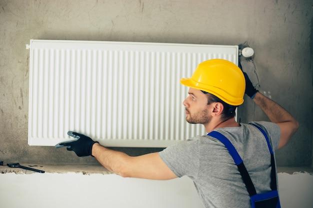 Молодой красивый профессиональный сантехник в современной униформе устанавливает радиатор отопления в новостройке под окном