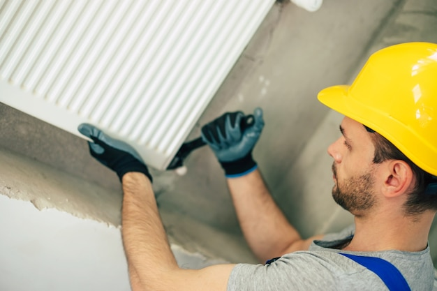 Young handsome professional plumber in modern uniform is installing heat radiator in a new building under window