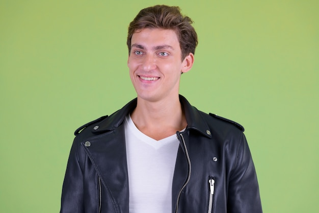 Young handsome rebellious man wearing leather jacket against green wall