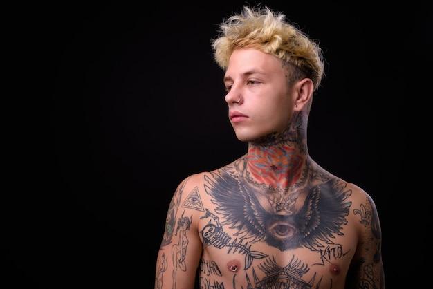 Молодой красивый бунтарь с татуировками без рубашки
