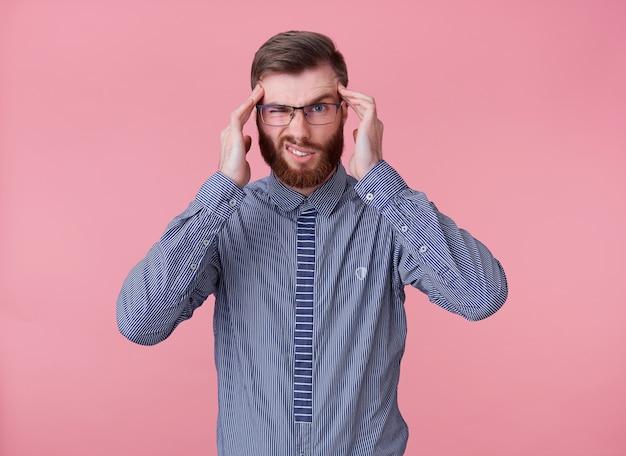 Молодой красавец рыжебородый в очках и в полосатой рубашке испытывает омерзительную головную боль, мигрень, раздражается - это невыносимо. стоит на розовом фоне.