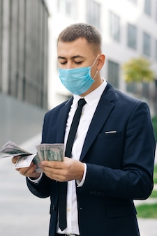 Young handsome rich man wearing stylish suit counting money standing in the street near office building