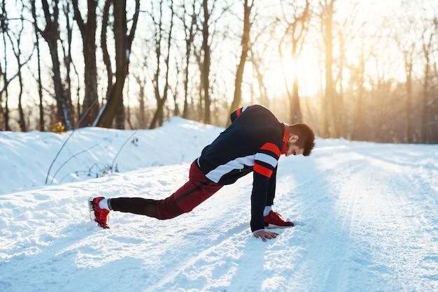 ハンサムなランナーが朝の雪に覆われた冬の道でヘッドフォンでウォーミングアップ。