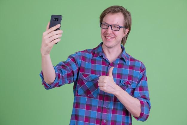 녹색 배경으로 크로마 키에 대해 안경 젊은 잘 생긴 스칸디나비아 힙 스터 남자
