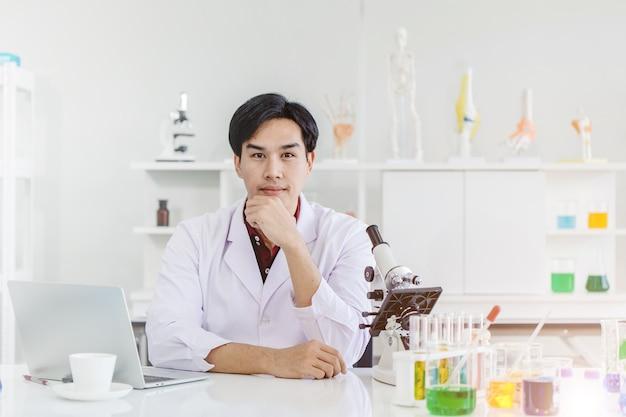 실험실 작업 책상에 앉아 젊은 잘 생긴 과학자
