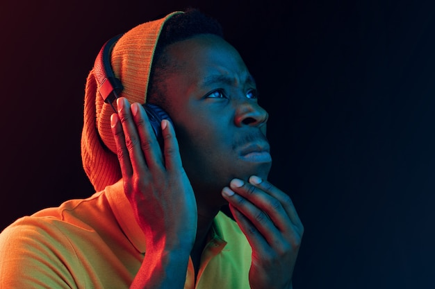 The young handsome serious sad hipster man listening music with headphones at black studio with neon lights. disco, night club, hip hop style, positive emotions, face expression, dancing concept